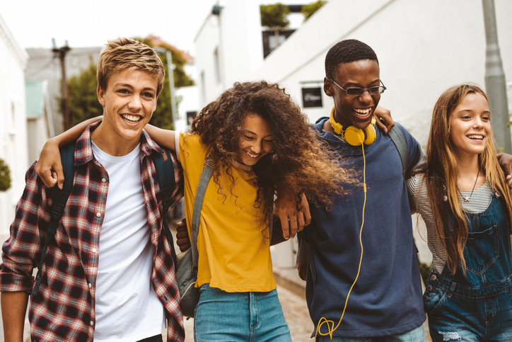 Teenage boys and girls walking in the street holding each other. Smiling college friends walking together in street wearing college bags having fun.