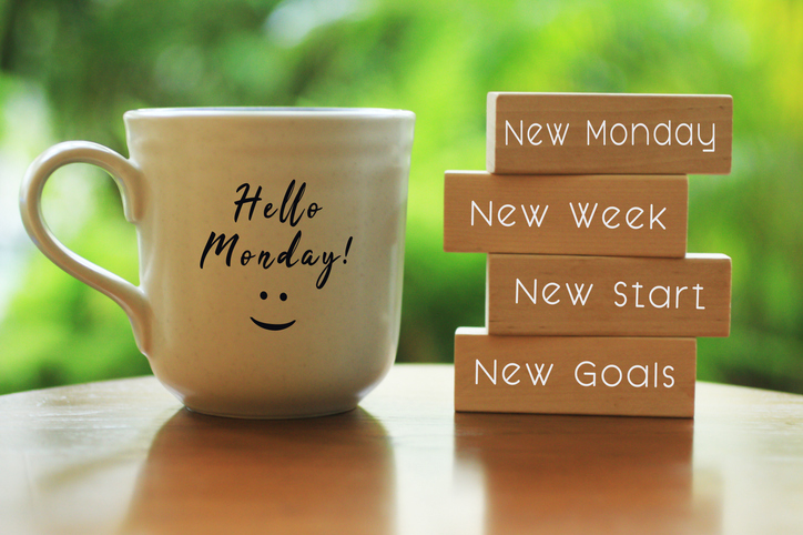 Hello Monday concept with inspirational motivational positive quote on wooden blocks - New Monday. New Week, New Start. New Goals. And a smiling face on a white morning cup of coffee or tea.