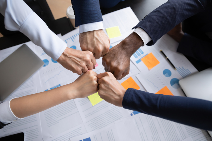 Teambuilding. Close up of multiethnic business team bumping fists above the table with documents in office showing collaboration, support, unity, partnership, motivation and effective work together