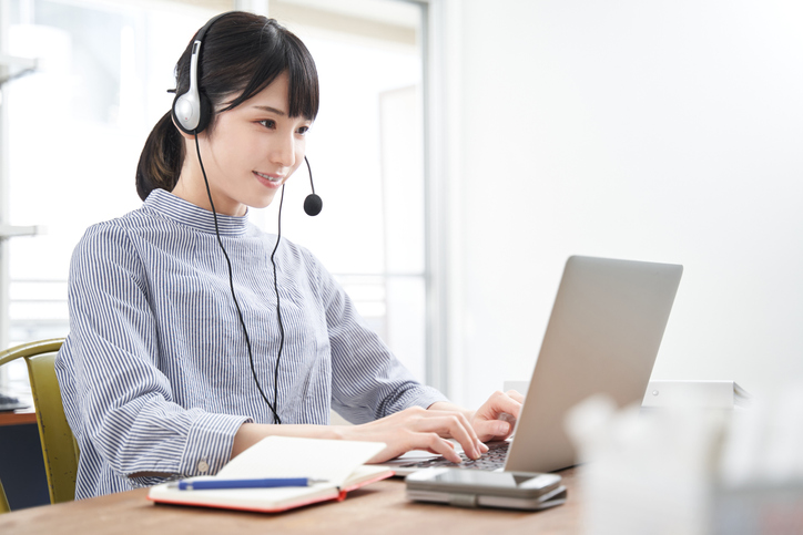 A plainclothes Japanese businesswoman in an online meeting at home