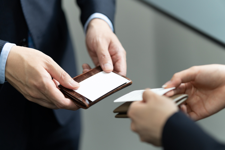 A close-up of a Japanese businessman exchanging business cards