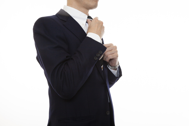 The upper body and front of a business person who wears a tie, white background