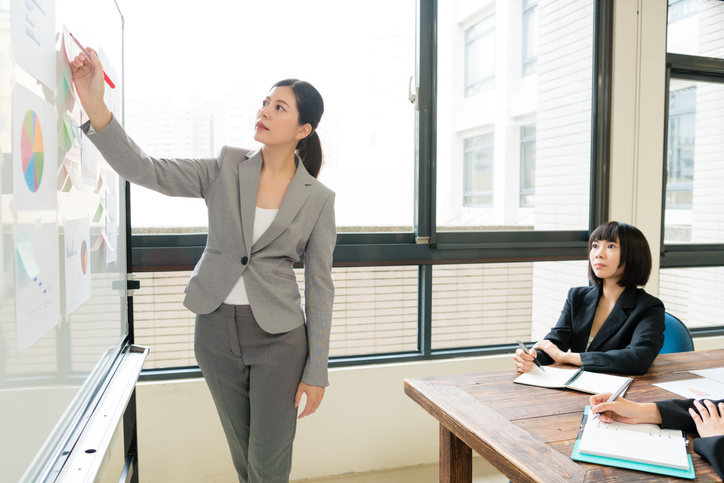 elegant attractive female office worker manager writing on document and explaining company marketing analysis report when she with colleague using whiteboard meeting in office.