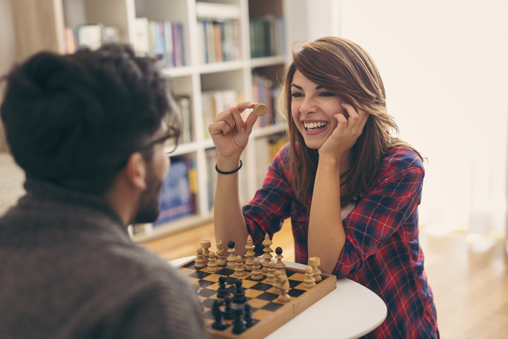 Couple in love sitting on a living room floor, playing chess and having fun