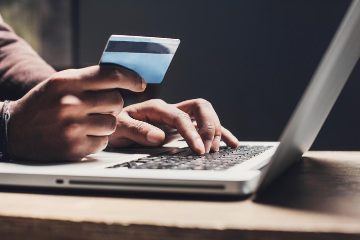Men entering credit card information using laptop computer keyboard. Online shopping concept