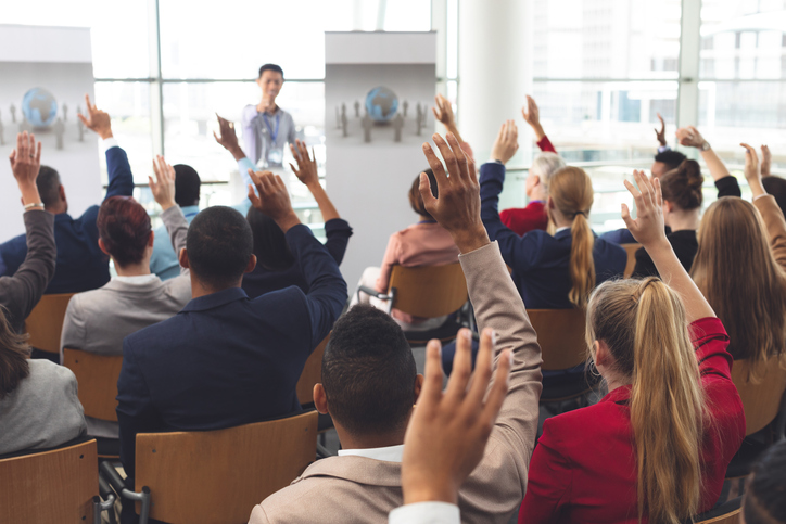 Rear view of diverse business people raising hands while they are sitting in front of Asian businessman at business seminar in office building