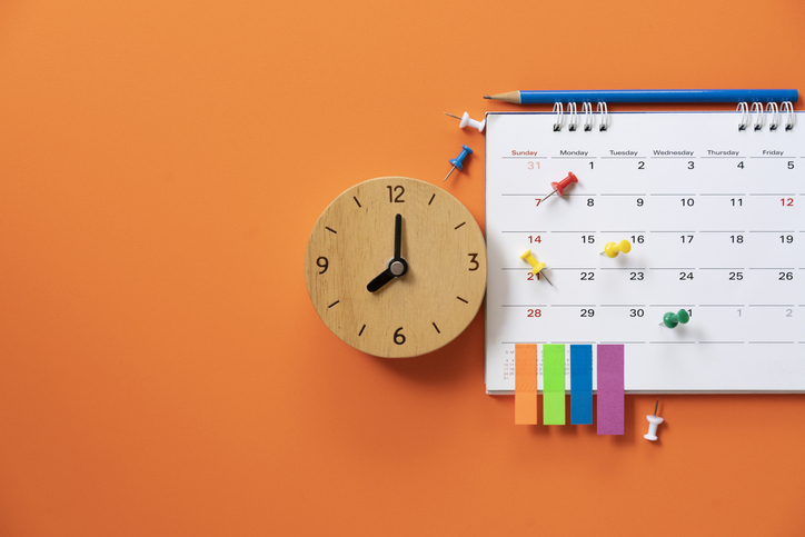 close up of alarm clock and calendar on the orange table background, planning for business meeting or travel planning concept
