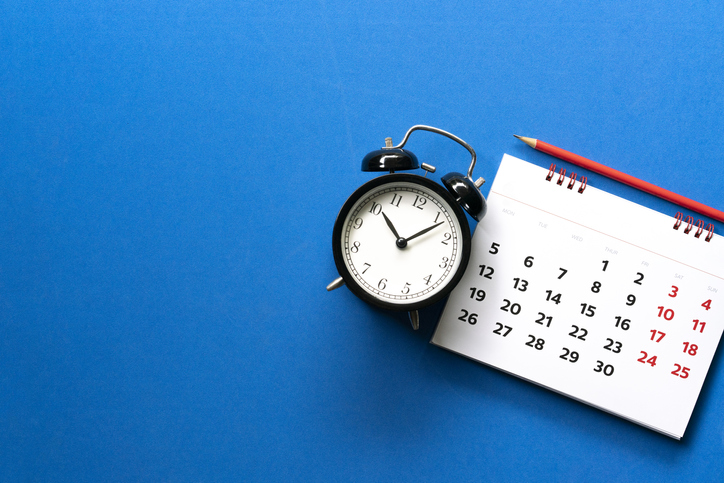 close up of calendar, alarm clock, pencil on the blue table background, planning for business meeting or travel planning concept