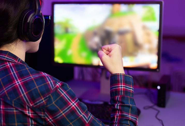 Female gamer winning in online video game and celebrating victory, wearing headphones