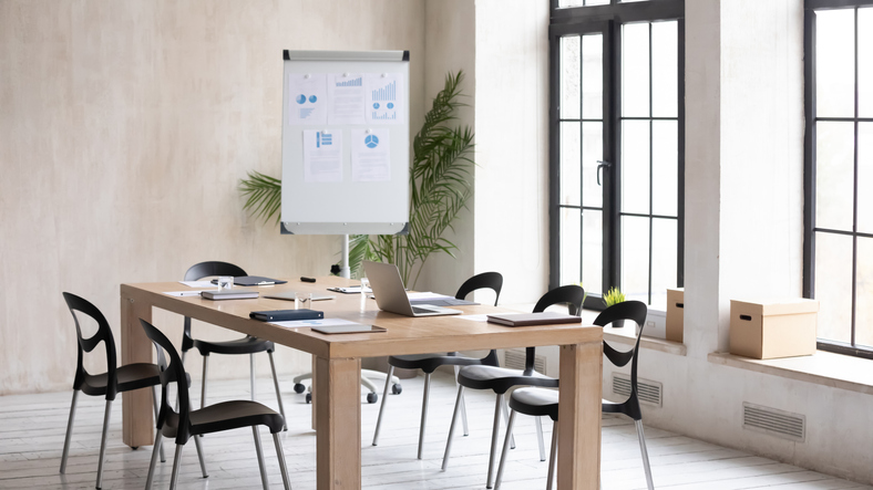 Empty modern loft office space with wooden table, electronic appliances notebooks ready for meeting, working workplace with no people prepared for briefing, whiteboard presentation or training