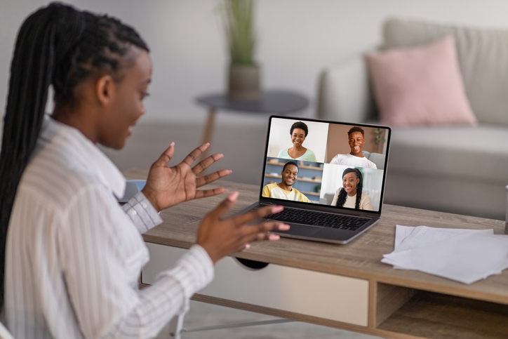 Online lesson, family communication or meeting with colleagues during covid-19 lockdown. Cheerful young african american lady gesturing, look at laptop and have conference call with friends on screen