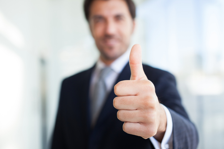 Portrait of a smiling businessman giving thumbs up