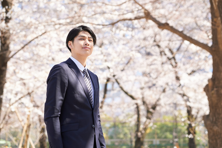 A smiling Japanese businessman stands with a cherry blossom in the background.
