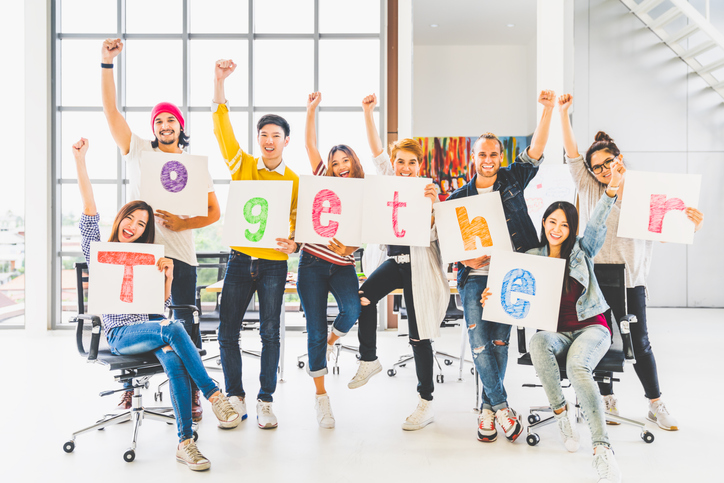 Multiethnic diverse group of office coworkers or creative team cheering and celebrating, holding letter banner papers written together word. Colleague partner teamwork, team building, empowerment, or friendship togetherness concept