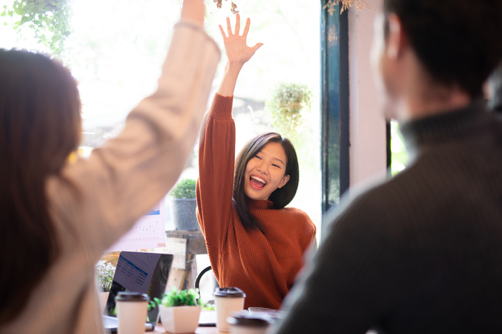 Asian woman and her team hand raised for happy winning success in coffee shop with team