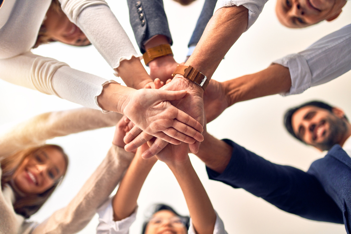 Group of business workers standing with hands together at the office