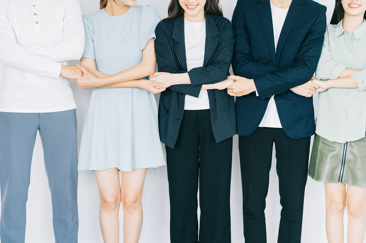 Asian young business people are holding hands to show solidarity