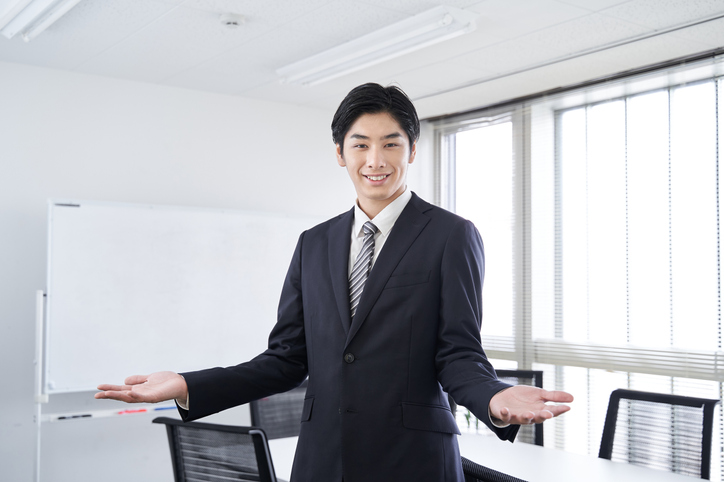 A Japanese male businessman smiles and spreads his hands in a meeting room