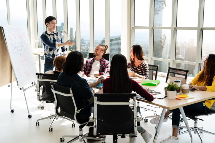 Young asian creative businessman standing and making presentation at modern office happy talking and brainstorming with team. Casual people business meeting concept.