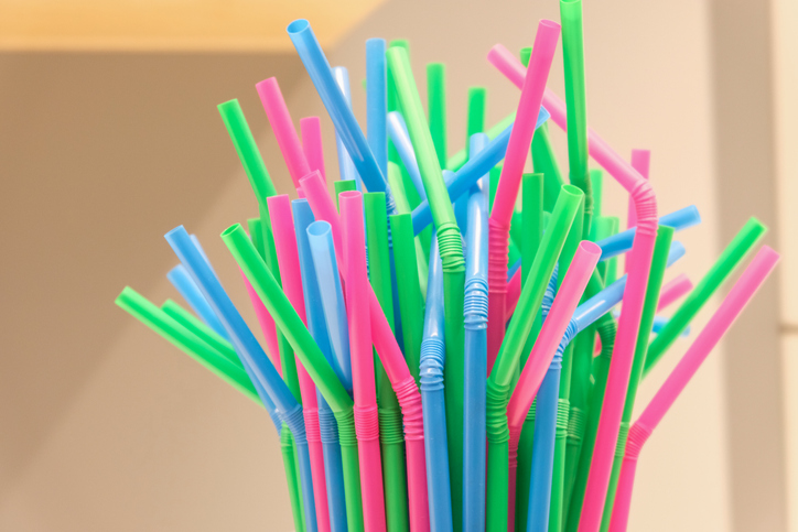 Top of several drinking straws made of plastic with different colors with blurred background