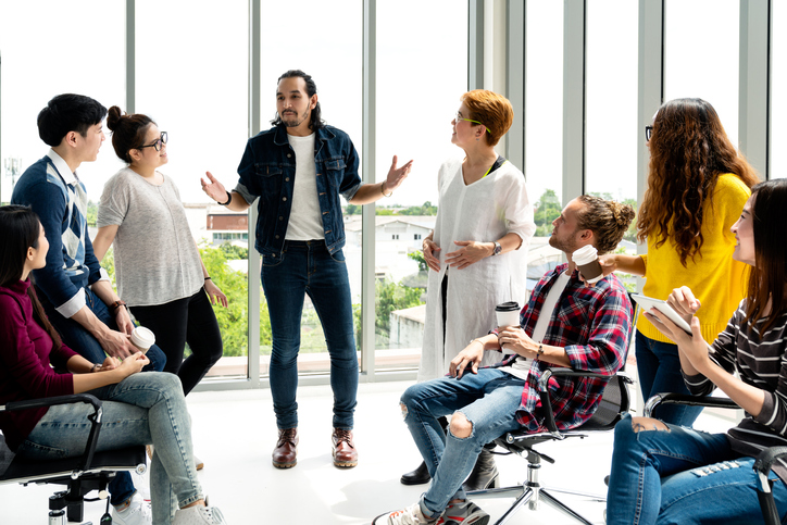 Attractive young multiethnic group talking at relax zone in coffee break time at office. Young asian hipster man sharing lifestyle idea to staff friends with fun and happy in happy workplace concept.