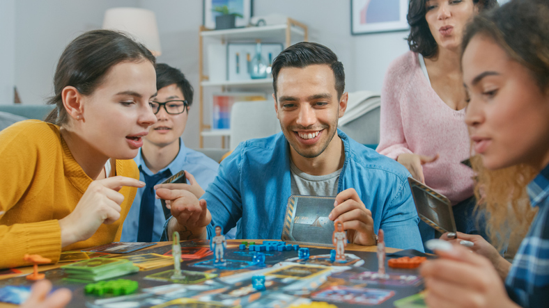 Diverse Group of Guys and Girls Playing in a Strategic Uniquely Designed Board Game with Cards and Dice. Friends Having Fun Reading Cards, Joking, Making Moves and Laughing in a Cozy Living Room