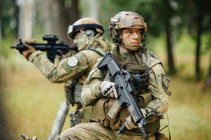 team of soldiers go through the woods and watch