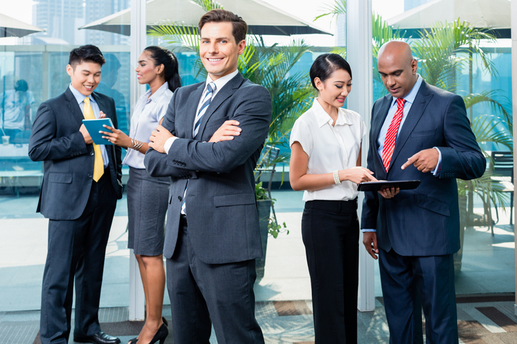 Business executive in front of his team of mixed ethnicities, Caucasian, Indian, Chinese, and Indonesian