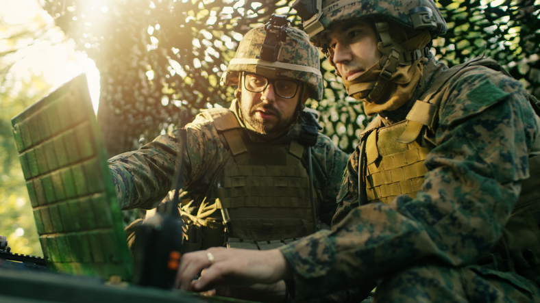 Military Staging Base, Officer Gives Orders to Chief Engineer, They Use Radio and Army Grade Laptop. They're in Camouflaged Tent in a Forest. They're on Reconnaissance Operation/ Mission.