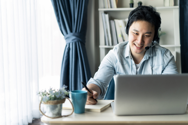 Asian businessman talking to colleague team in video call conference writing note on book with smile face. Man using computer laptop and headphone for online meeting. Smart working from home concept.